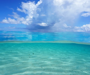 Half and half, Pacific ocean seascape, shallow sandy seabed underwater with cloudy blue sky over the water, French Polynesia