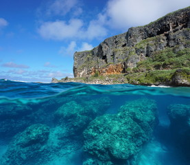 Half and half over and under the water surface, coastal cliff and rocks underwater split by waterline, Pacific ocean, Rurutu island, Austral archipelago, French Polynesia