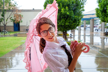 Girl with Tie and Large Glasses Stands Under Pink Umbrella