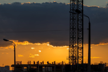 Construction workers silhouettes, cranes and building construction site against sunset sky.