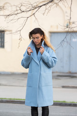 Girl in a blue coat holds the collar in the city
