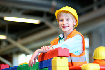 Happy boy in safety helmet plays indoors. Schoolchild building house with toy construction bricks. Safety education for children. Playful work experience for young kids.
