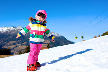Happy child enjoying winter vacation in Alpine resort in Austria. Little girl playing in the snow. Active sportive toddler learning to ski.