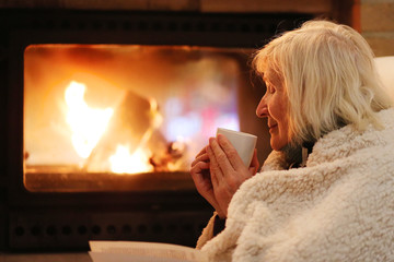 Happy senior woman, wrapped in warm knitted plaid, relaxing at home in the evening, sitting in rocking chair, drinking tea, reading book and enjoying fireplace - successful retirement concept