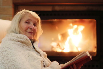 Happy senior woman, wrapped in warm knitted plaid, relaxing at home in the evening, sitting in rocking chair by fireplace and reading a book - successful retirement concept