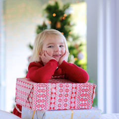 Portrait of little girl in festive red dress with big gifts boxes under decorated christmas tree. Cute kid in Xmas mood enjoying family celebration.