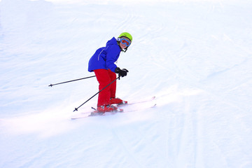 Happy child enjoying winter vacation in Alpine resort. School boy skiing in the mountains. Active sportive teenager learning ski technics.