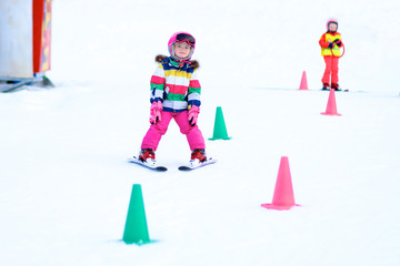 Happy child enjoying winter vacation in Alpine resort in Austria. Active sportive toddler girl learning to ski. Kid having fun in ski school sliding snowplow and turning left and right.