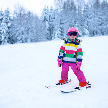 Happy child enjoying vacation in Alpine resort in Austria. Little girl skiing in mountains. Active sportive toddler wearing helmet and glasses learning to ski. Winter sport for family.