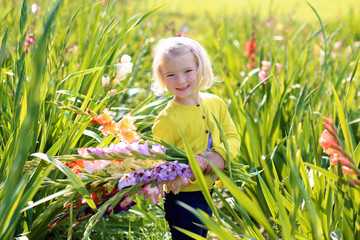 Little blonde girl holding bouquet of gladiolus flowers. Child enjoying nature playing in blossoming field. Cute kid picking fresh flowers in the garden in late summer or early autumn.
