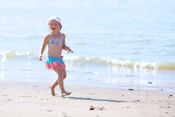 Adorable toddler girl in pretty  swimsuite playing with toys on wide sandy beach