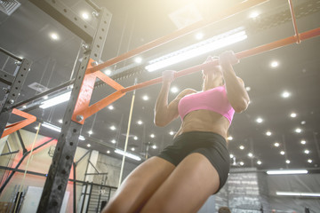 Muscular fitness woman doing exercises.Concept of healthy lifestyle. Cross fit bodybuilder in the gym
