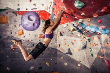 young woman climbing artificial boulder indoors