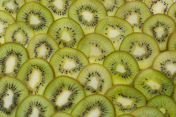 Bright green background with slices of juicy kiwi. Healthy food