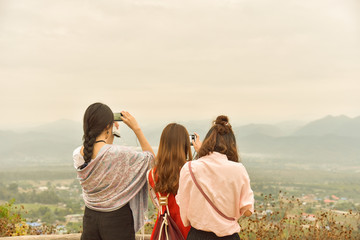 Three of asian ladies enjoy mountain view,use smart phone captur