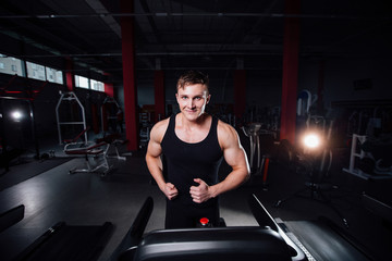 Young strong big man fitness model in the gym running on the treadmill with water bottle.