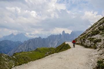 View of cyclist riding mountain bike on trail in Dolomites,Tre C