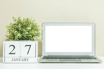 White wooden calendar with black 27 january word with white blank space at center of computer notebook on white wood desk and cream wallpaper textured background , selective focus at the calendar