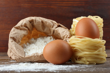 Raw pasta, eggs and flour on a wooden table.The concept of cooking.