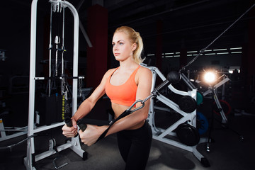 young fitness woman demonstrate crossover exercises. The pectoral muscles, hard training with exercise-machine Cable  gym