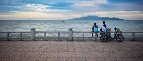 Two young friend's sitting together enjoying the view over the south china sea and vinperl island Vietnam.