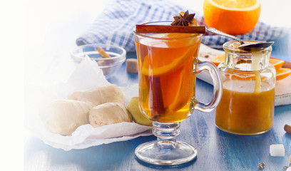 Ginger tea with orange and honey in glass cup.