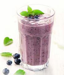 Glass of blueberry smoothie with mint.