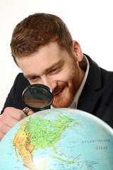 Junger Mann untersucht mit Lupe die Weltkugel