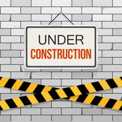Simple white sign with text 'Under Construction' hanging on a gray brick wall with warning tapes. Grunge brickwork background. Building, engineering concept. Creative template for web design