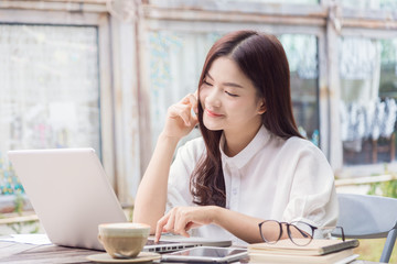 young happy casual asian woman using technology on her laptop co