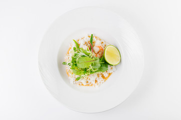 Crab with chili sauce, lime, parsley and rice on a plate on a white background, top view