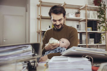 Father feeding his baby in home office