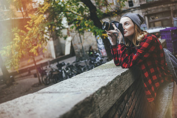 Young woman taking pictures with reflex camera