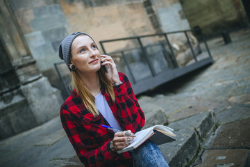 Spain, Barcelona, portrait of smiling young woman on the phone sitting on stairs with notebook