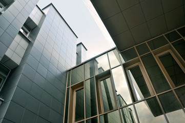 Look up at the modern facade of glass and wall panels.
