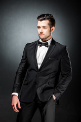 portrait of confident handsome man in black suit with bowtie posing in dark studio background