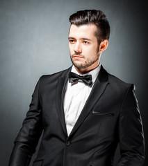 portrait of confident handsome man in black suit with bowtie posing in dark studio background