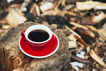 Cute red cup of fresh morning coffee on the wooden stump background