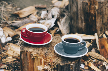 Two cups of fresh coffee on the tree stump outdoors