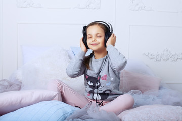 Child schoolgirl sitting on a bed and listening to music.