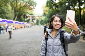 Woman taking photo by mobile phone in Meiji Shrine