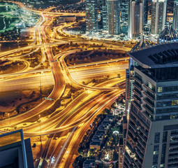 Aerial view of large highway junction in Dubai, UAE, at night with city illuminations and scrapers. Colorful travel and transportation background.