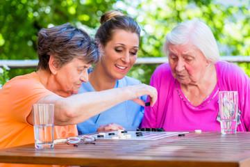 Seniorinnen spielen Brettspiel mit Altenpflegerin im Altenheim
