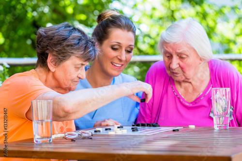 seniorinnen spielen brettspiel mit altenpflegerin im. Black Bedroom Furniture Sets. Home Design Ideas