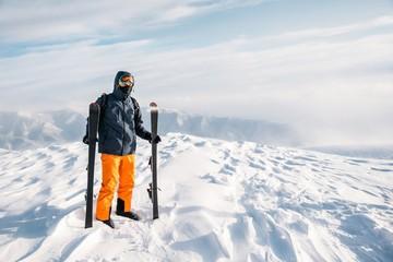 Skier standing on snowy mountain summit