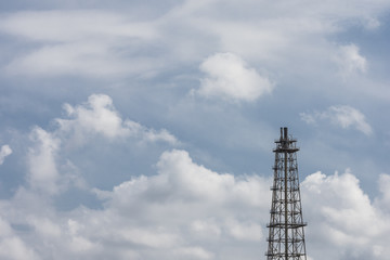 oil refinery - flare tower with a cloudy blue sky background