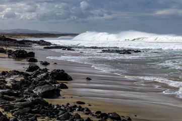 Massive waves, green turquoise colored, rolling in at a surf break on Fuerteventura Canary Islands.