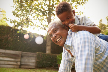 Young black boy climbing on his grandfather's back in garden