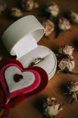 Gift for Valentine's Day an offer of marriage. Soft box with beautiful gold and diamond ring surrounded by dried roses and cute felt heart. Love is in the air on Valentine's Day