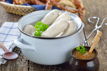 Frische Weißwürste im Topf mit Brezen und süßem Senf serviert - Hot Bavarian white sausages in an enamel cooking pot served on a wooden table with fresh pretzels and sweet mustard